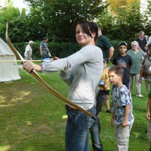 Foto junge Frau beim Bogen schießen auf einer Wiese mit anderen Besuchern