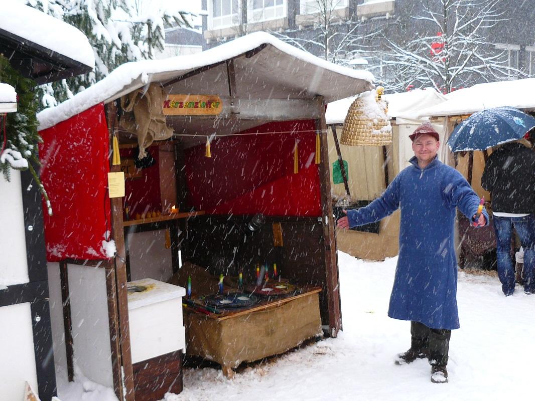 Foto Kerzenzieherei im Winter auf einem Weihnachtsmarkt bei Schneefall
