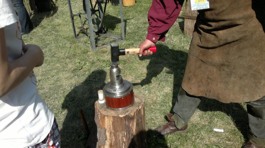 ich schlage mit einen Hammer auf den Prägestempel