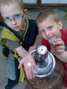 die zwei Kinder, Jungen, zeigen ihre frischen und neuen Glücksthaler