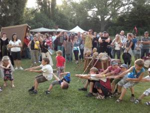 Tau ziehen, Seil ziehen, viele Menschen und Besucher, Marktstände und Zelte auf einer Wiese