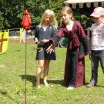 drei Mädchen beim spielen mit Hufeisen, auf einer schönen grünen Wiese, auf einem mittelalterlichen Fest im Sommer