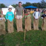 Sack hüpfen auf einem mittelalterlichen Fest, auf einer grünen Wiese im Sommer, ein Mann und 5 Kinder